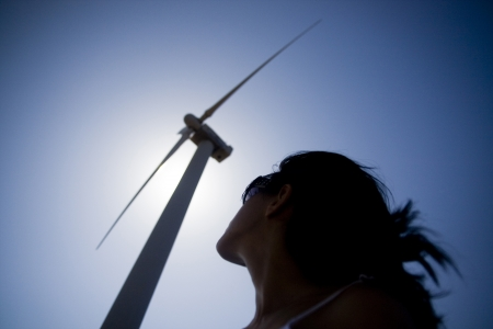 View of a young girl watching the windmill. Stock Photo