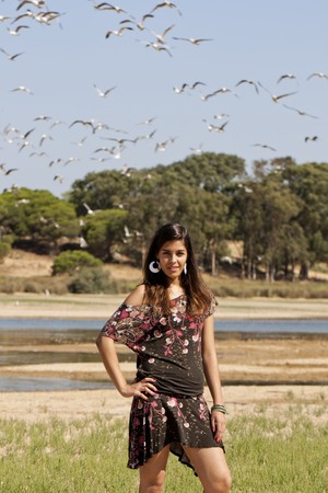 Beautiful girl with floral dress posing on a forest with lots of birds. photo
