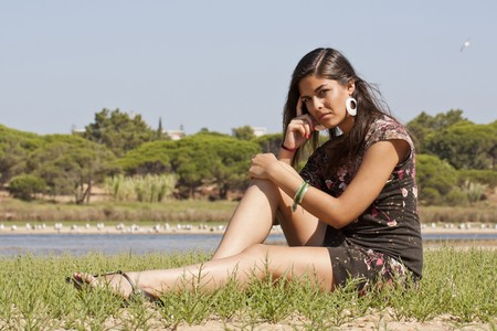 Beautiful girl with floral dress meditating on the nature. photo