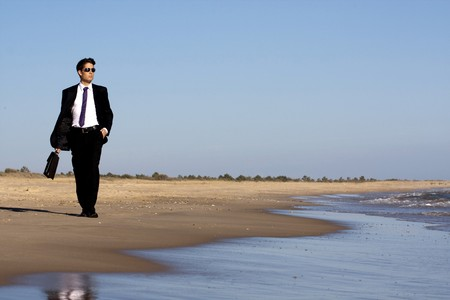 Close up view of a bunisess man in a dark suit walking on the beach.