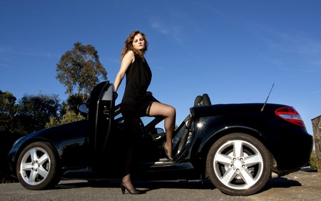 view of a beautiful woman exiting a sports car. photo