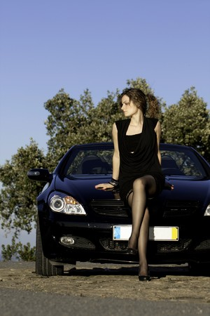 view of a beautiful woman next to sports car on a fashion pose. Stock Photo - 8263567