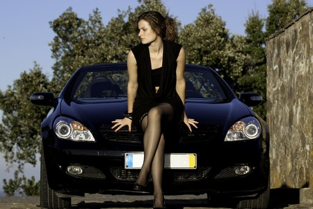 view of a beautiful woman next to sports car on a fashion pose. photo