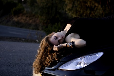 view of a beautiful woman on top of a sports car. photo