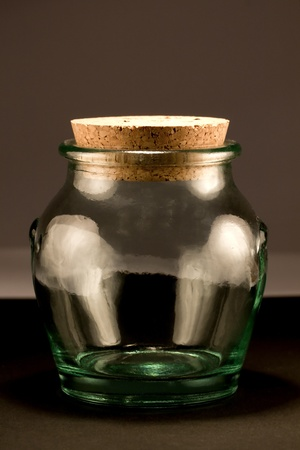 unlabelled: Close view detail of a glass jar isolated on a dark background. Stock Photo