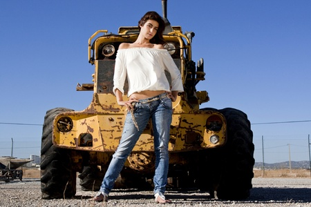 View of a beautiful girl on a fashion pose in front of a construction tractor. photo