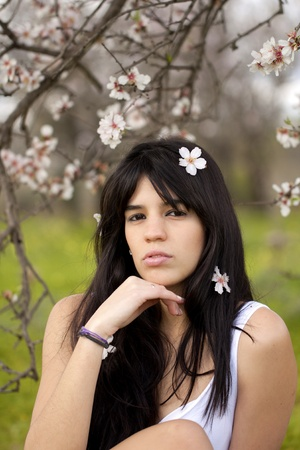 View of a beautiful girl on a white dress on a green grass field next to a almond tree photo