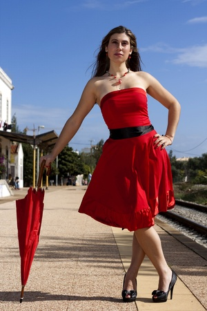 View of a beautiful woman with red dress and umbrella photo