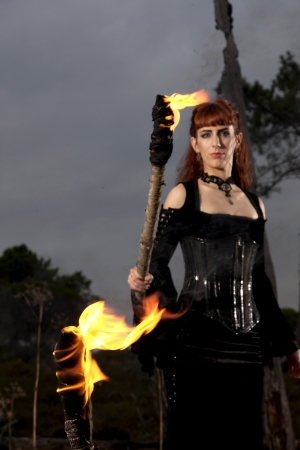 log hair: View of a dark clothed woman with a torch on her hands.