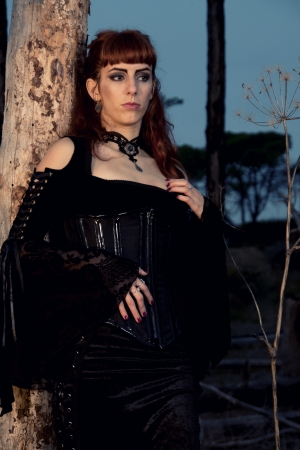 Dark gothic woman with dark clothes posing on the night forest. Stock Photo - 9050665