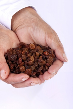 Close view of a pair of hands holding some raisins isolated on a white background. photo