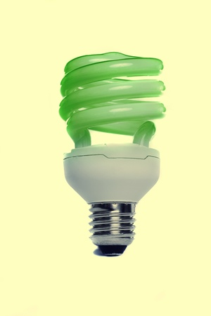View of a energy efficiency light bulb isolated on a yellow background.  photo