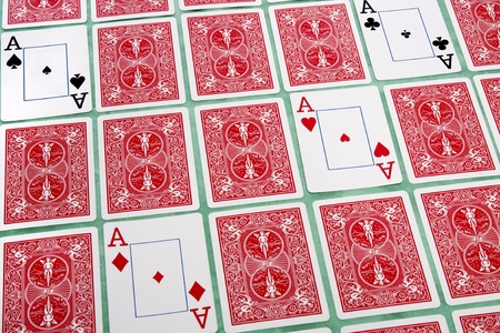 Close up view of a bunch of flipped playing cards spread on a green cloth table.