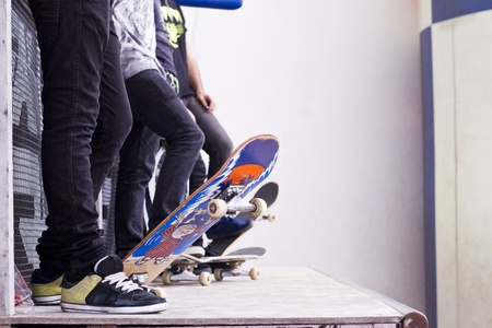 View of a bunch of skaters with skate boards on a pipe. photo