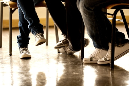 high schools: View of some teenager legs on a classroom.