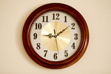 Close up view of a kitchen clock hanging on the wall. photo