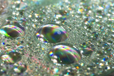Close up view of many colorful and bright drops of water on a shiny surface. Stock Photo