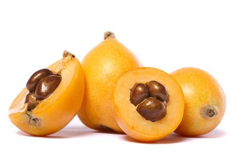 Close up view of some loquat fruit isolated on a white background.