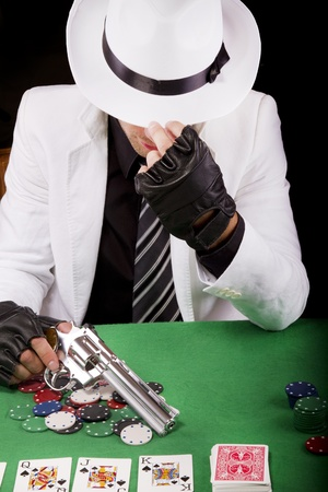 View of a gangster man playing some cards and poker, holding a gun.