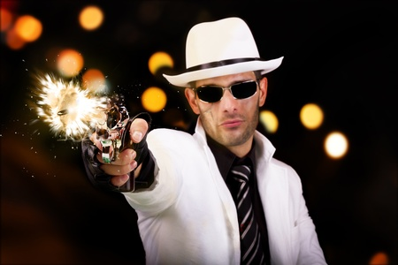 muzzle flash: View of a gangster man with a scar, firing a gun, we can see the bullet.
