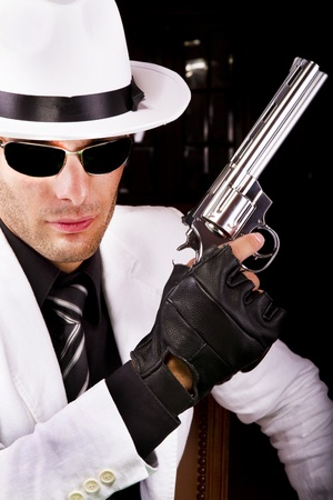 View of a white suit gangster man holding a gun. photo