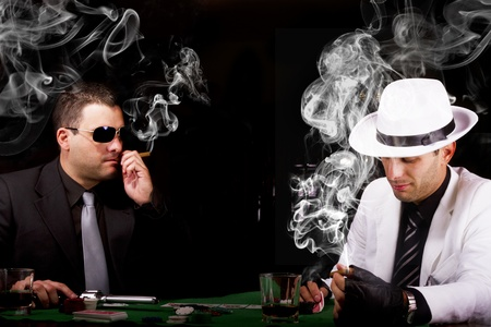 View of two gangster males playing some poker and smoking Cuban cigars. photo