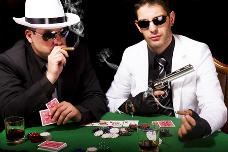 View of two gangster males playing some poker and smoking Cuban cigars.