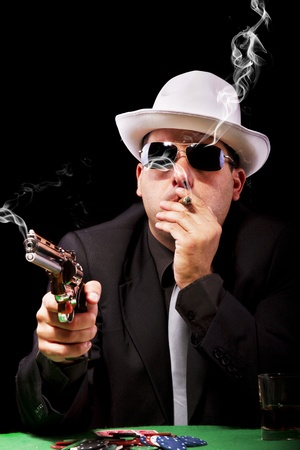 View of a gangster man playing some cards and poker, smoking a Cuban cigar. photo