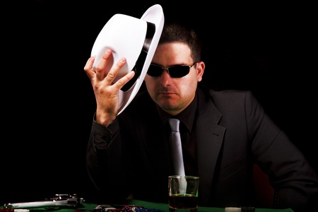 View of a gangster man playing some cards and poker, holding a white hat. photo