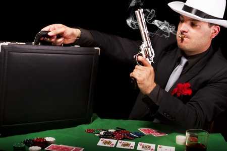 View of a white suit gangster man holding a gun and a briefcase.