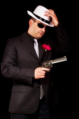 View of a dark suit gangster man holding a gun. photo