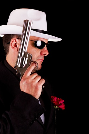 View of a dark suit gangster man holding a gun. photo