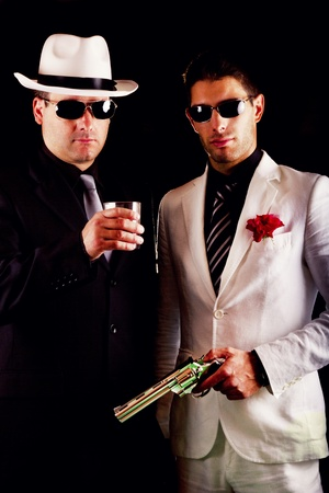 View of two gangster males holding a gun on a black background. photo