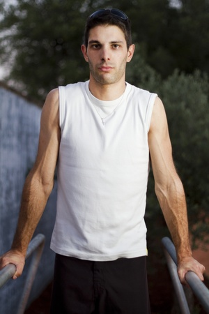 Close view of a young man doing exercise on a park. photo
