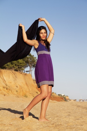 View of a beautiful young girl playful with a purple dress in the beach. Stock Photo - 10408883