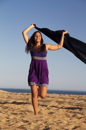 View of a beautiful young girl playful with a purple dress in the beach. photo