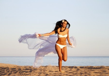 View of a beautiful young girl with a white bikini running on the beach. photo