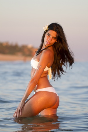 View of a beautiful young girl with a bikini standing on the shore. photo