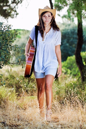 View of a beautiful young country girl with a guitar on the woods.  photo