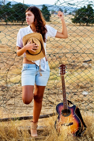View of a beautiful young country girl with a guitar on the fence of the grassland.  photo