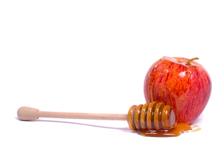 Close up view of a royal gala apple with a honey dipper isolated on a white background.