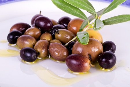 Detail view of some olives on a plate, with leafs from the tree. photo