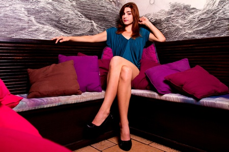 View of a beautiful young girl on a blue dress inside a bar pub. Stock Photo - 12210495