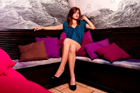 View of a beautiful young girl on a blue dress inside a bar pub. Stock Photo - 12210470