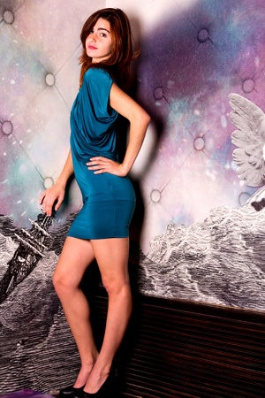 View of a beautiful young girl on a blue dress inside a bar pub. photo