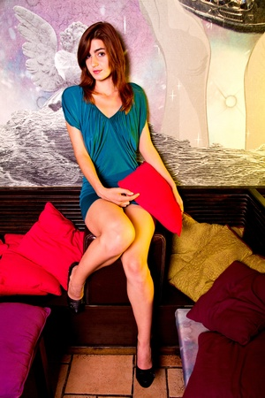 View of a beautiful young girl on a blue dress inside a bar pub. Stock Photo - 12210590