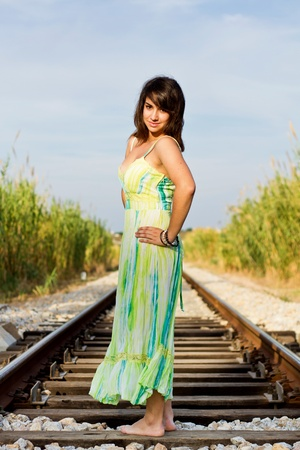 View of a beautiful girl with a spring dress on a railway. photo