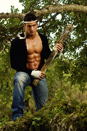 View of a fighter male holding a mace weapon on a forest. photo