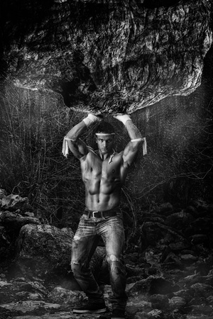 View of a fighter male holding a giant rock. Stock Photo - 12212272