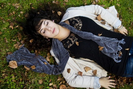 lies down: Beautiful young girl lies down on the green grass with fallen leaves.